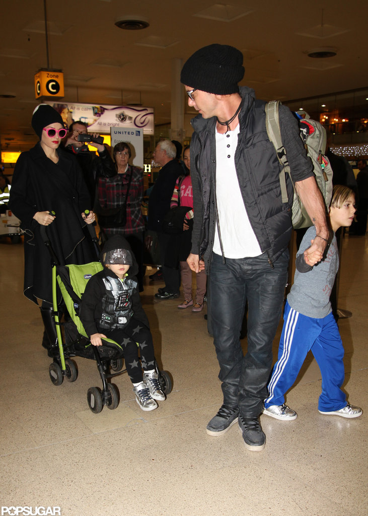 Gavin Rossdale held hands with Kingston Rossdale while Gwen Stefani pushed Zuma Rossdale through the airport in London.