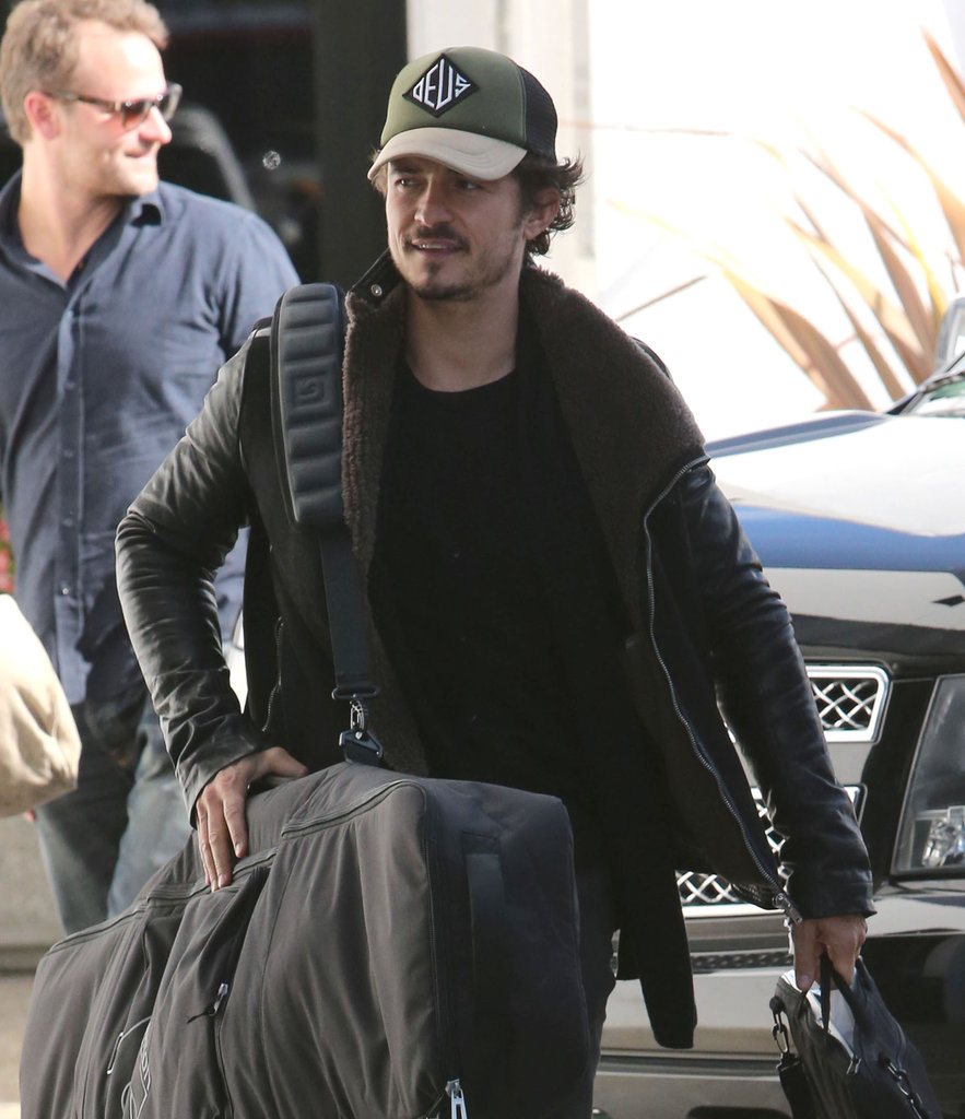 Orlando Bloom carried a snowboard bag to a private plane at LAX.