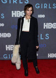 Zoë Kravitz layered up in black and white, accenting her look with a vintage cross necklace.