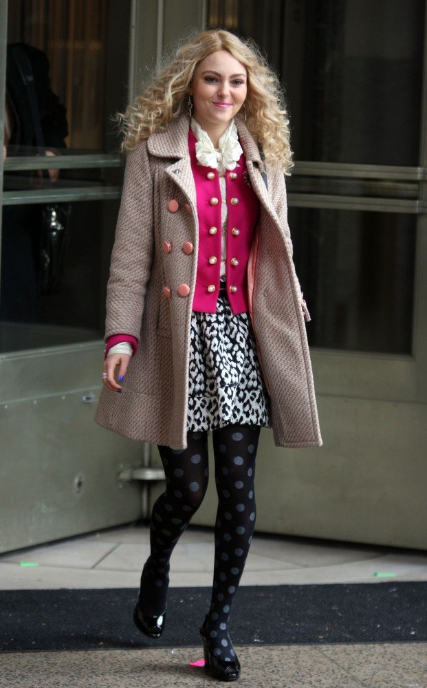 Carrie layered up in a pink cardigan, leopard skirt, polka-dot Hue tights, and a textured peach coat.