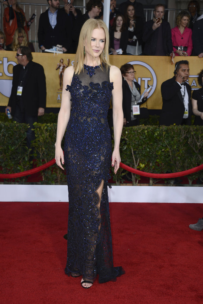 Nicole Kidman turned up the shine in a dark blue Vivienne Westwood gown, complete with dazzling embellishments, a thigh-high slit, and sheen finish. Black strappy sandals, pink nail polish, and glistening emerald earrings completed her red-carpet look.
