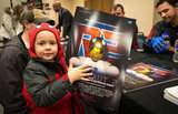 A boy and his poster of NASA's Robonaut.  Source: Flickr User NASA HQ
