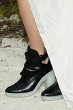 "To give her white high-low dress a ""grungier"" feel, Rita Ora wore a pair of black-and-white cutout ankle boots."