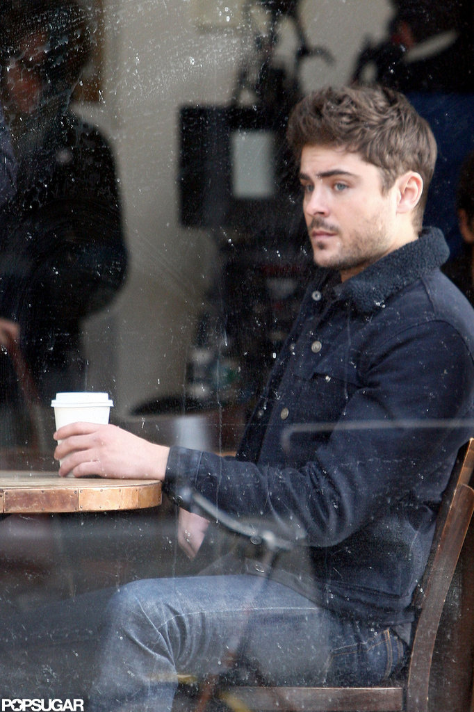 Zac Efron sat in a coffee shop on set.