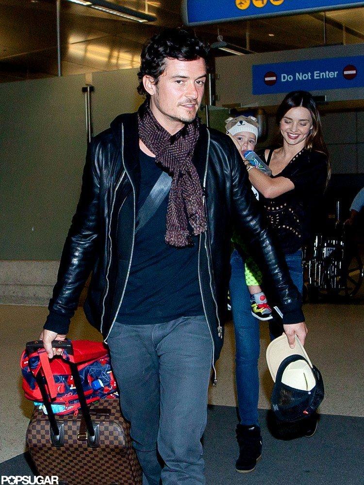 Miranda Kerr held Flynn Bloom as she arrived at LAX with husband Orlando Bloom.