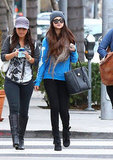 Selena Gomez accessorized her cheeky skeleton sweater and fold-over leather boots with a fringed knit Cooperative scarf, charcoal gray beanie, and Dolce & Gabbana tote while shopping around LA.