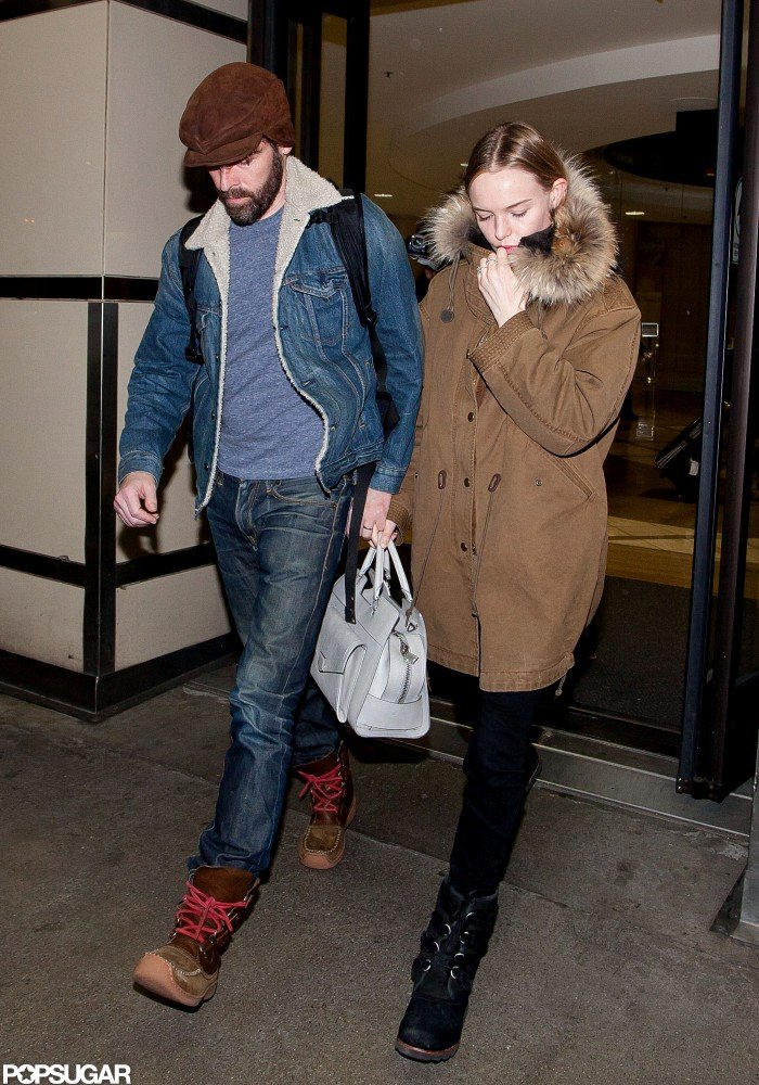 Kate Bosworth kept warm in a jacket with a fur hood as she held hands with fiancé Michael Polish at LAX.