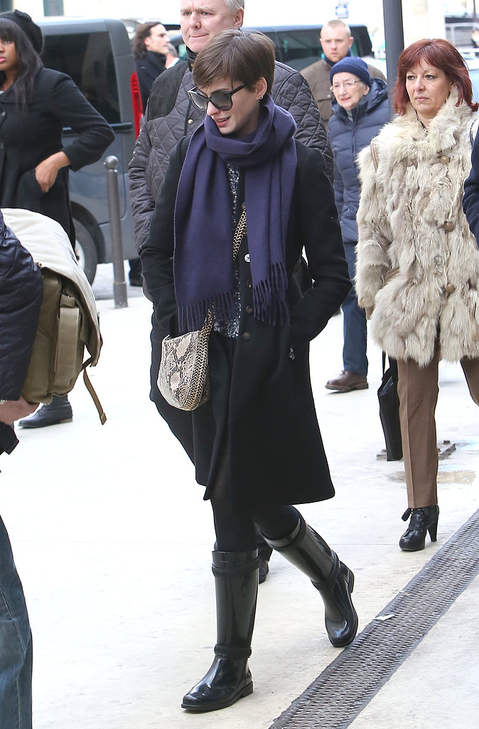 Anne Hathaway's purple scarf and faux python Stella McCartney bag instantly pepped up her bundled-up Parisian style.