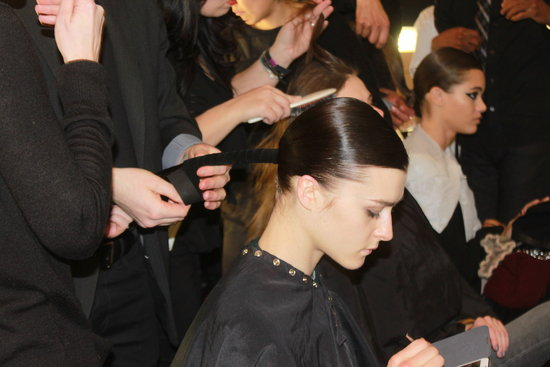 Odile Gilbert for Kérastase first blow-dried hair straight and slicked it back into a ponytail with a deep side part using the brand's Double Force hair spray for sleekness. Then the low pony was wrapped with suede ribbon and secured with elastic. Finally, the taut piece was twisted into a chignon.