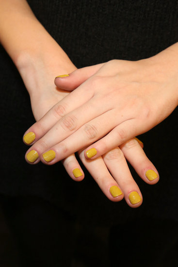Deborah Lippmann painted the nails using a new shade from the Punk Rock collection, I Wanna Be Sedated. The mustard yellow shade looks like normal polish in the bottle, but comes out with a gritty texture that dries semimatte, so there was no top coat. The collection launches this July, and is part of a growing trend: textured manicures.