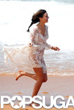 Miranda Kerr ran on the beach in a white dress.