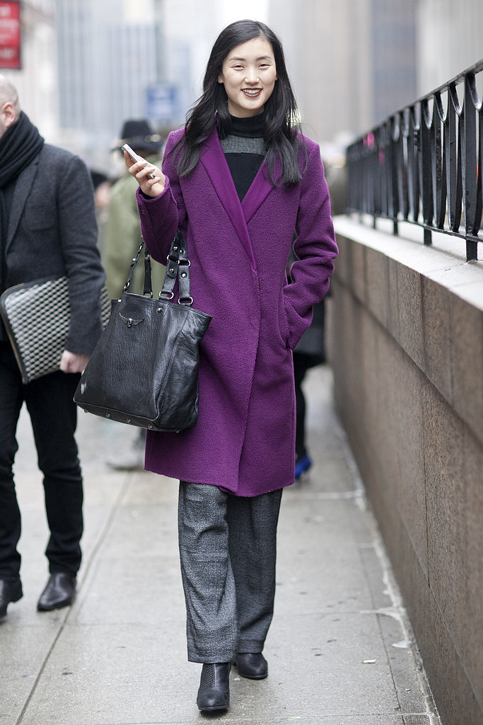 A plum-hued coat contrasted her moody charcoal grays.