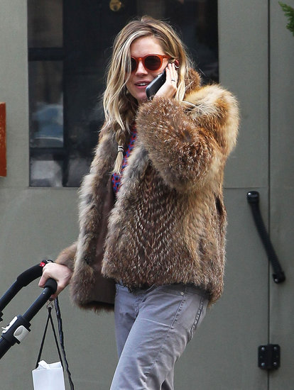 Sienna Miller pushed a stroller while talking of the phone.