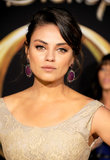 Mila decked her ears out with magenta earrings that popped against her beige dress.