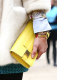 A bright yellow clutch injects a burst of color against a cozy white coat.
