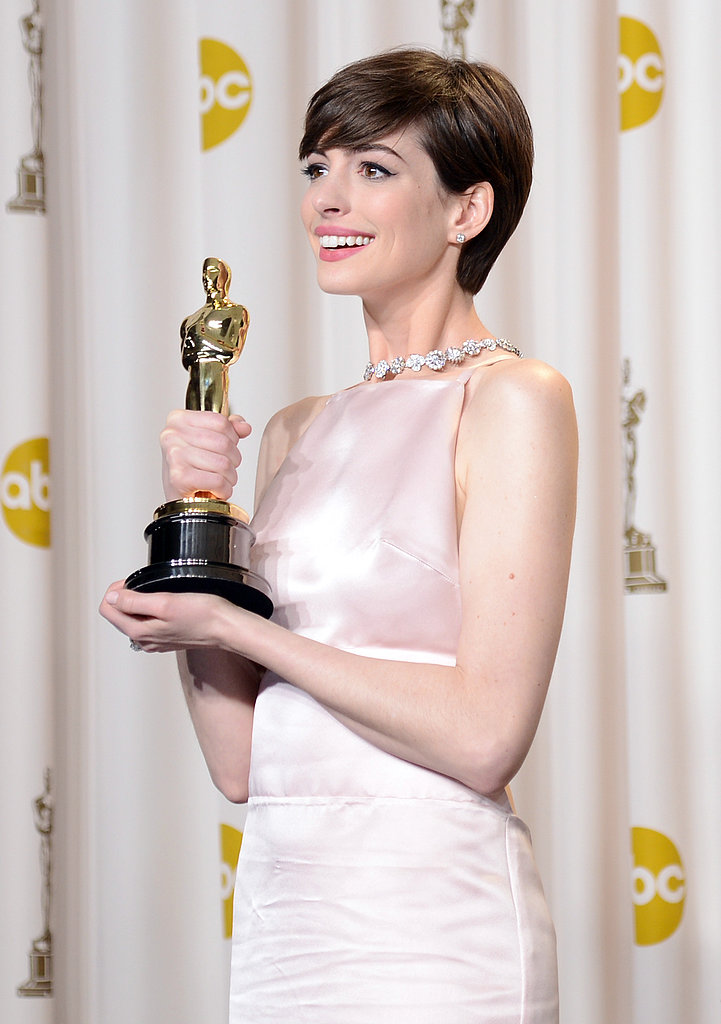 Anne Hathaway presented her award to the press.