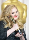 Adele held up her award in the Oscars press room.