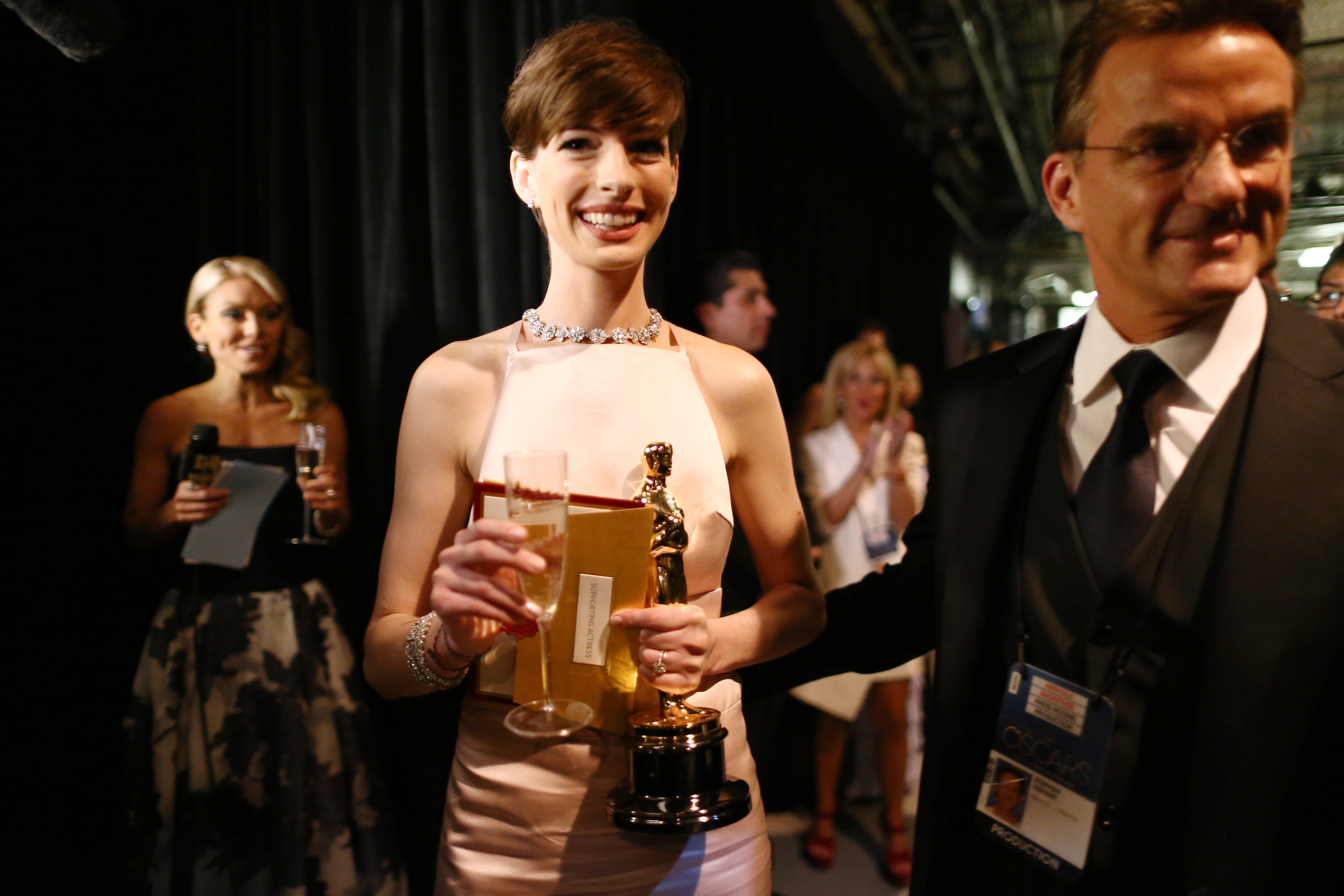 Anne Hathaway juggled her Oscar, a glass of champagne, and her winning envelope backstage after her win.