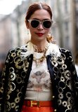 Glittery gold sunglasses completed this opulent Fashion Week outfit.