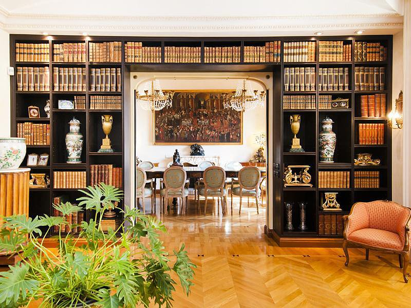Brightly colored books and unique figurines pop against the dark bookshelves, while an orange armchair adds an extra punch. Source: Sotheby's