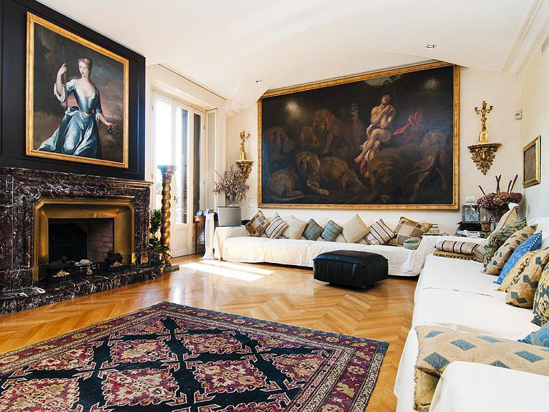 The expansive living room features beautiful hardwood floors, oversize artwork, and sleek, pillow-lined couches for a refined, upscale look. Source: Sotheby's