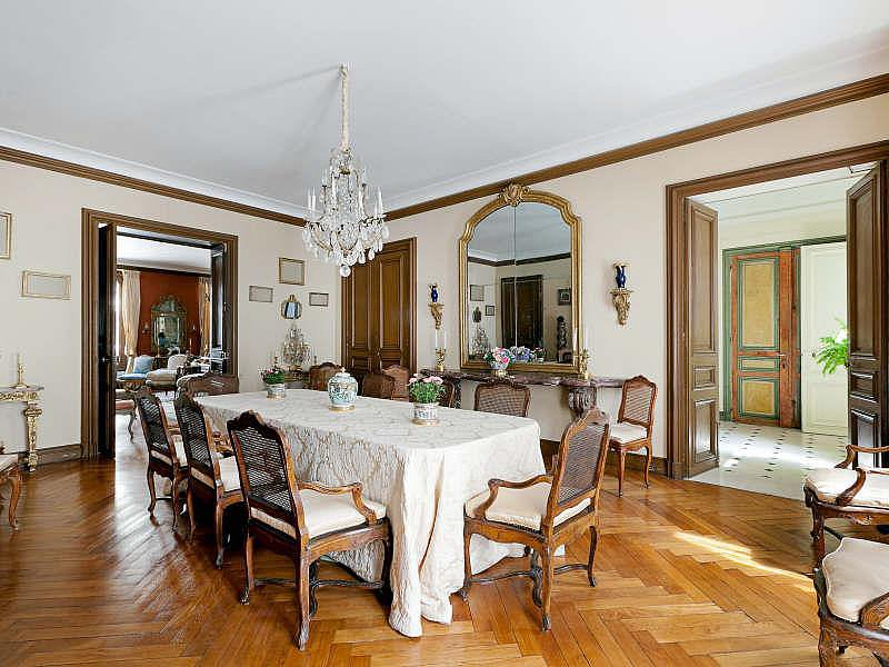 The dining room has a decidedly vintage style, with antique chairs, a lace tablecloth, and a traditional chandelier. Source: Christie's Real Estate