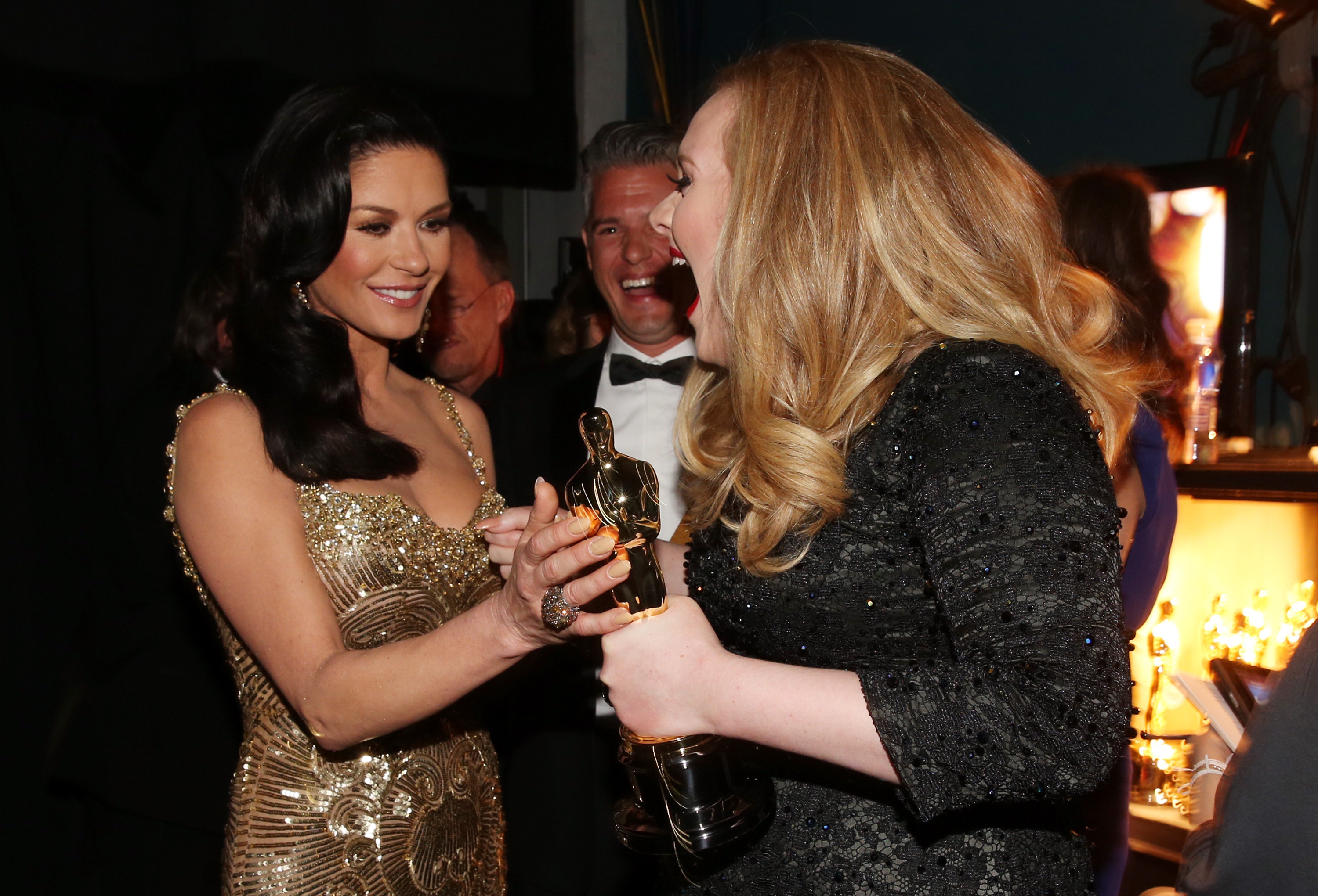 Adele celebrated her win with Catherine Zeta-Jones at the Oscars.