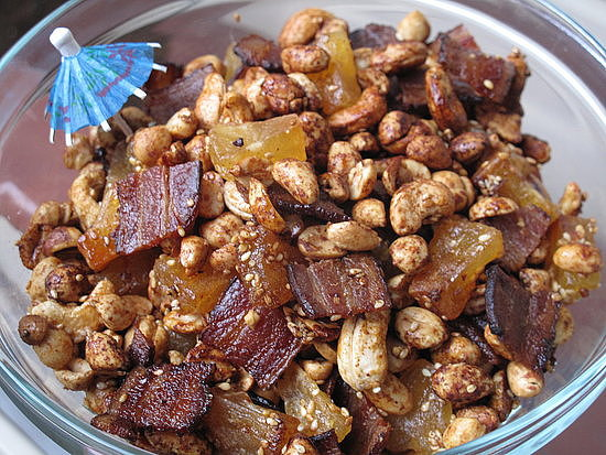 Enjoy an addicting blend of sweet, salty, and savory with this tiki snack mix recipe, which mixes bacon, nuts, and candied pineapple.