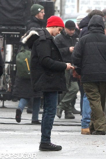 Andrew Garfield bundled up in a red beanie and black coat on the set.