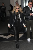 En route to PFW, Fergie donned flared leather pants with a black-and-white striped blazer and wool cape.