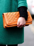 A camel woven clutch added an old-school touch and stood out against this emerald-green coat.