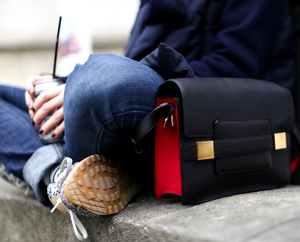 A black and red satchel adds polish to even the most casual outfit.