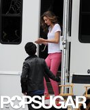 Miranda Kerr rubbed lotion on her arms while leaving her trailer.