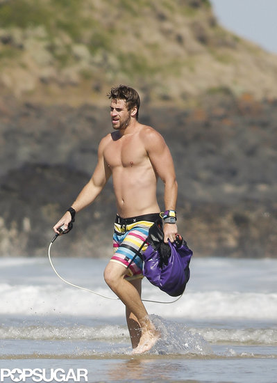 Shirtless Liam Hemsworth Flexes His Muscles on the Beach