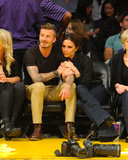Victoria Beckham sat front-row with her husband, David, for a May 2012 Lakers game wearing wide-legged dark denim jeans and high-heeled boots.