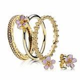 PANDORA gold channel set diamond ring $1,499, fine gold cherry blossom ring $349, fine gold floral ring $349, fine gold cherry blossom studs $199.