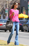 During a sunny day in LA, Alessandra Ambrosio showed off her bright side in a hot-pink sweater, which she paired with wide-legged jeans and a gray Givenchy bag.