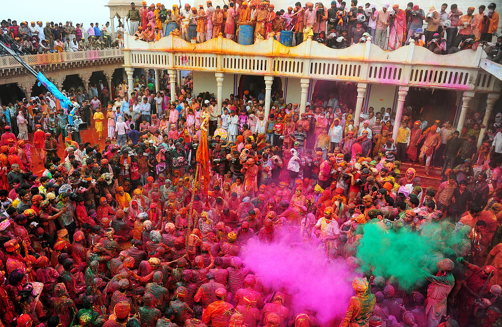 People threw colored powder at each other for the Lathmar Holi festival at the Nandji Temple in Nandgaon, India.
