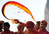 A man threw colored water at the Radha Rani Temple during the Lathmar Holi festival in Barsana, India.