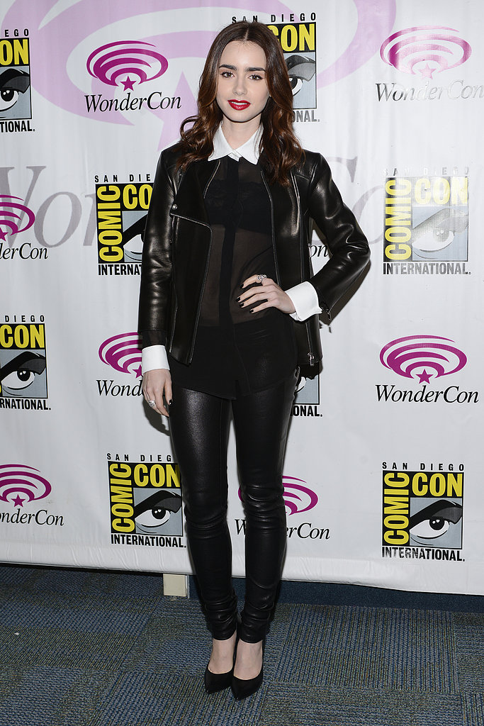 At WonderCon in Anaheim, Lily Collins stuck to a black and white color scheme in black leather pants, a black leather Michael Kors jacket, and a sheer black blouse with a white collar and cuffs.