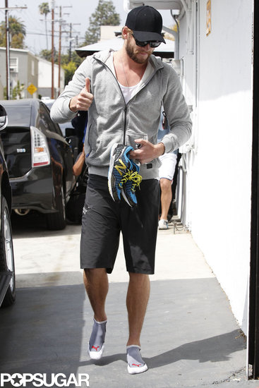 Liam Hemsworth wore a hat and shades.