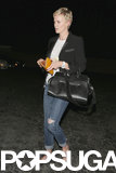 Charlize Theron held onto a yellow wallet.