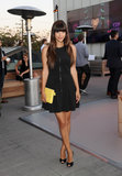 Hannah Simone looked equal parts sexy and sweet in a zipper-front LBD, black and white pumps, and a yellow Coach iPad sleeve-turned-clutch.