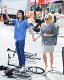 Sienna Miller and Tom Sturridge stood near two bikes.