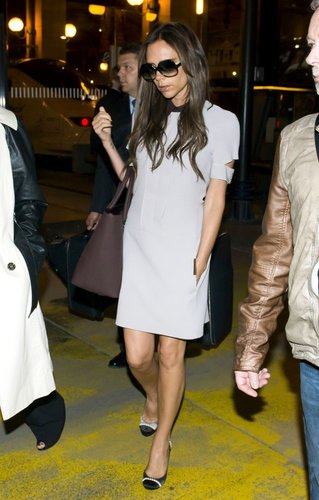 Victoria Beckham took Paris in a little white collared Victoria Beckham dress, her signature oversize sunglasses, a brown satchel, finished with dainty satin pumps.