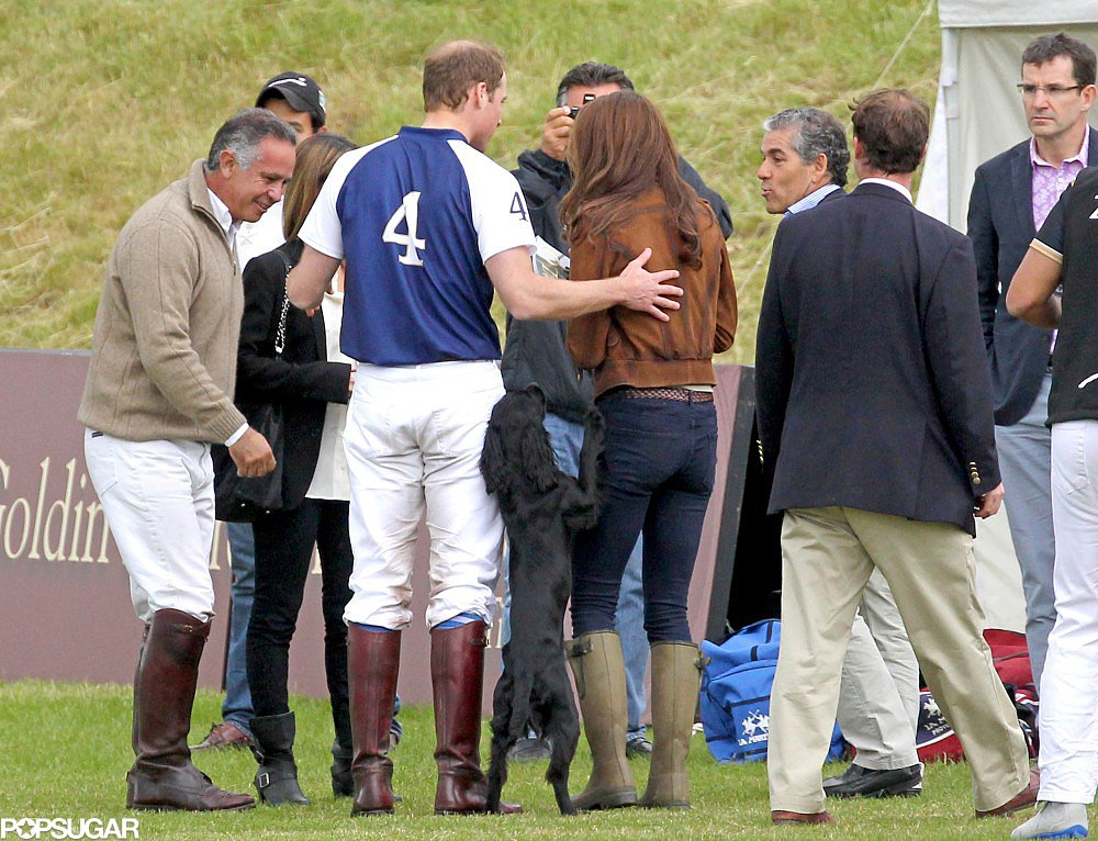 Prince William put his hand on Kate Middleton's back after his polo match in the UK in June 2012 while their pup, Lupo, looked on.