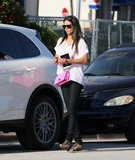 Adriana Lima's hot-pink crossbody bag added a bold pop of color to her black and white outfit in Miami.