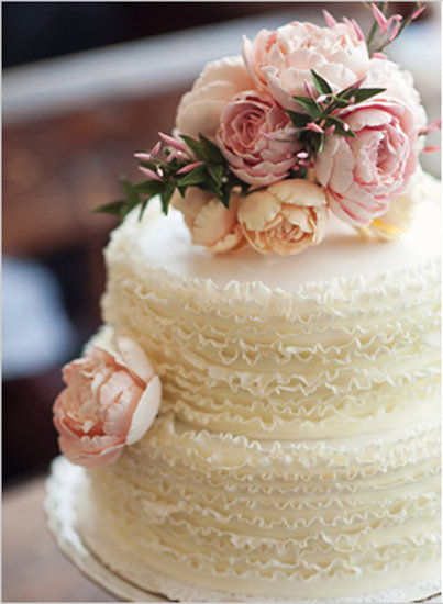 There's something so sweet about this simple but beautiful cake — the ruffles and flowers make the perfect classic combo.  Photo by Oh, Darling! via Wedding Chicks