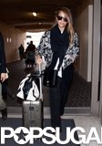 Jessica Alba arrived at LAX looking sporty-cool in this Isabel Marant floral bomber jacket ($933), a black-and-white Chloé bag, and red Jenni Kayne d'Orsay flats.