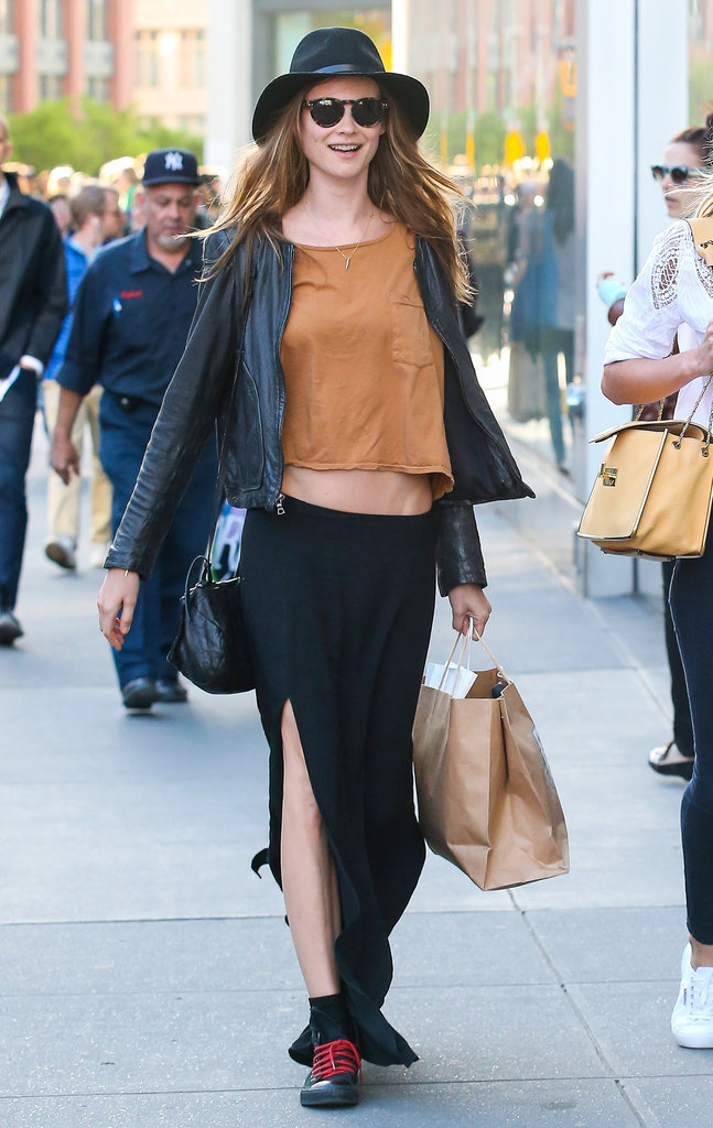 Behati Prinsloo went grunge in a black maxi skirt with a thigh-high slit, a cropped tee, black leather jacket, a black fedora, round sunglasses, and black sneakers with red laces.